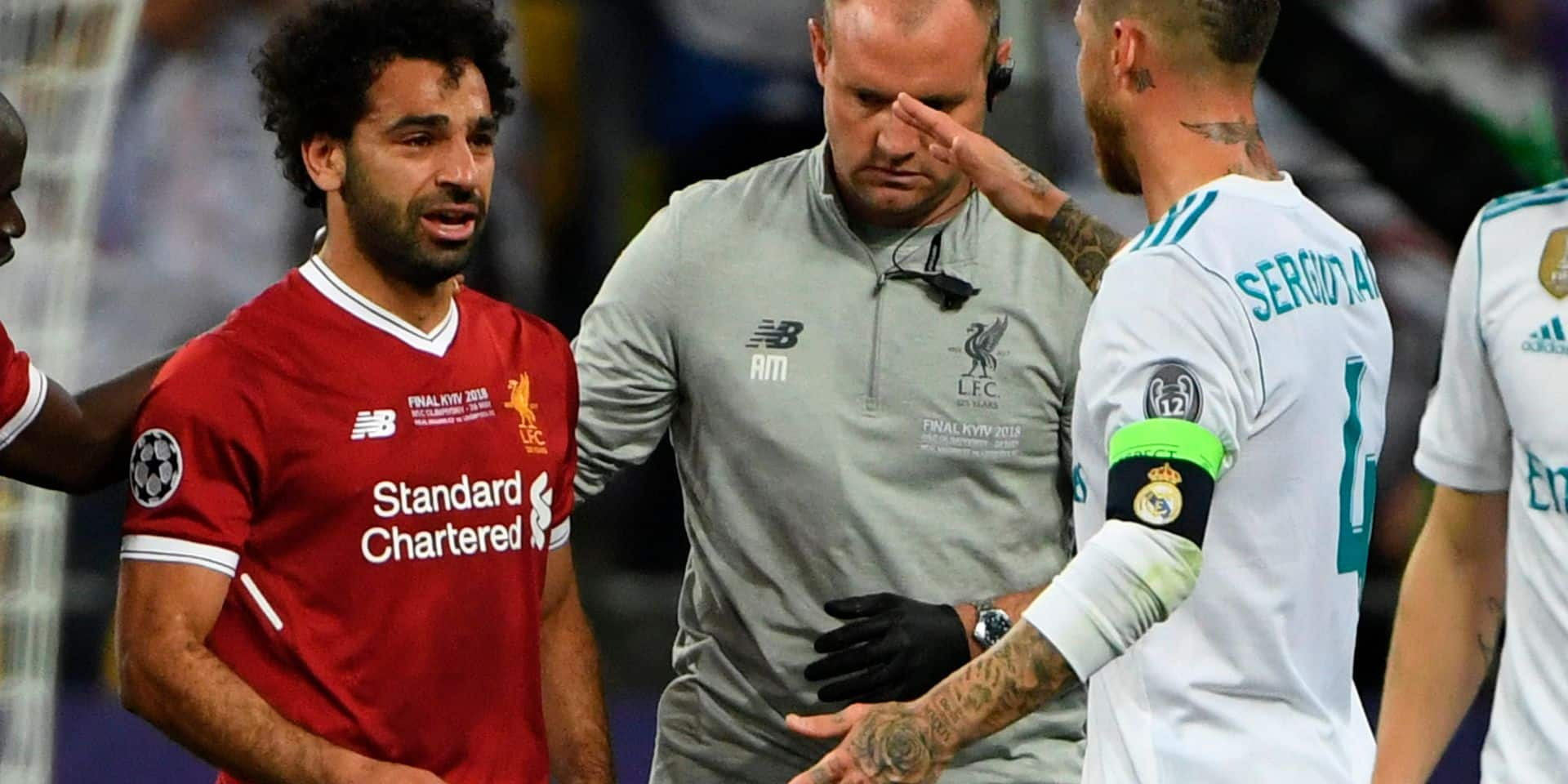 Real Madrid's Spanish defender Sergio Ramos (R) comes over to console Liverpool's Egyptian forward Mohamed Salah (L) who has been forced the leave the pitch after hurting his shoulder in a challenge with Ramos during the UEFA Champions League final football match between Liverpool and Real Madrid at the Olympic Stadium in Kiev, Ukraine on May 26, 2018. / AFP PHOTO / Paul ELLIS