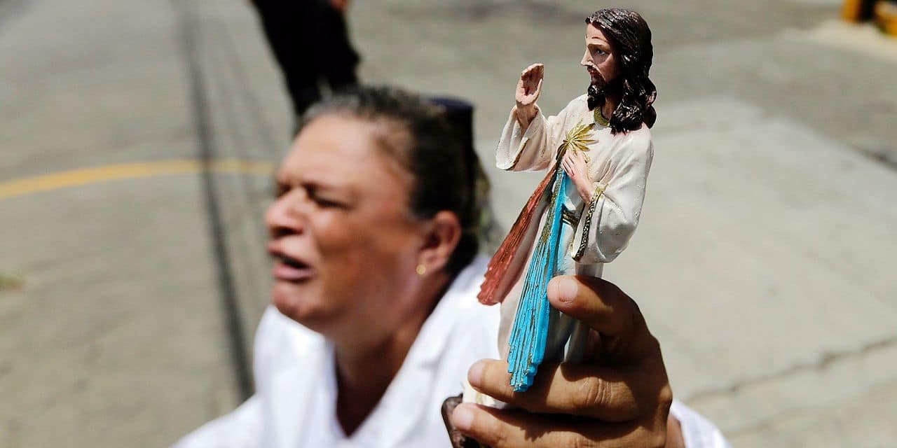 A woman kneels holding a religious figure as a caravan of the Catholic Church, including cardinal Leopoldo Brenes, passes by in Diriamba, Nicaragua, on July 9, 2018. Hundreds of under-pressure Nicaraguan President Daniel Ortega supporters broke into the basilica in an opposition heartland on Monday and harassed Roman Catholic bishops at the heart of a mediation process. The attack came a day after at least 14 people died in a raid by a pro-government mob in the areas of Diriamba and Jinotepe, 20 km from the opposition bastion of Masaya, in the Central American country's southeast. / AFP PHOTO / Inti OCON