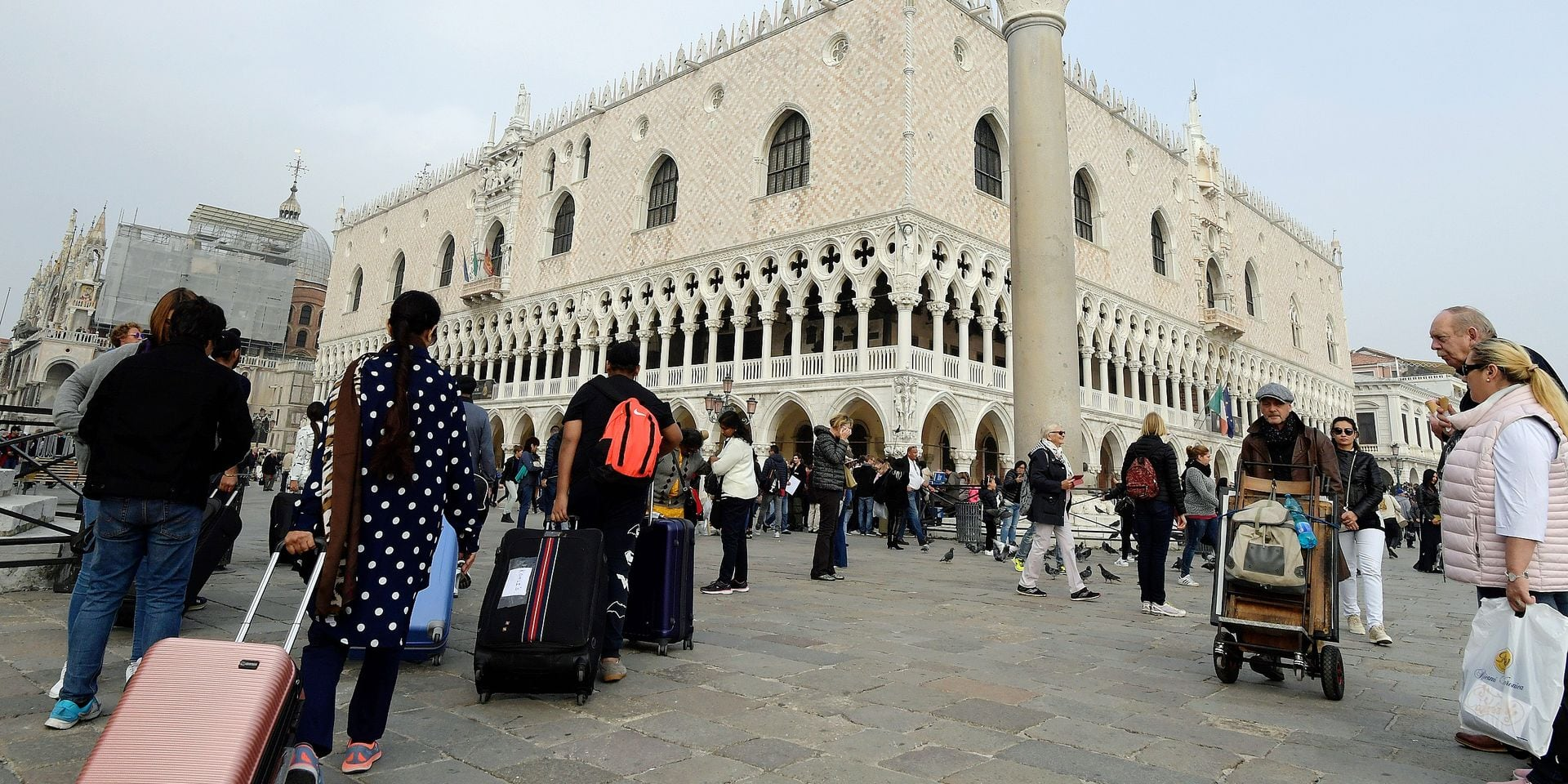 """A picture taken on October 20, 2017 in Venice shows tourists arriving in front of the """"Palazzo Ducale"""" at St Mark's square. - A referendum will be held on October 22, 2017 in the Italian regions of Lombardy and Veneto, both ruled by rightwing party Northern League, to ask for more fiscal autonomy and more powers to decide how to allocate financial resources. (Photo by MIGUEL MEDINA / AFP)"""