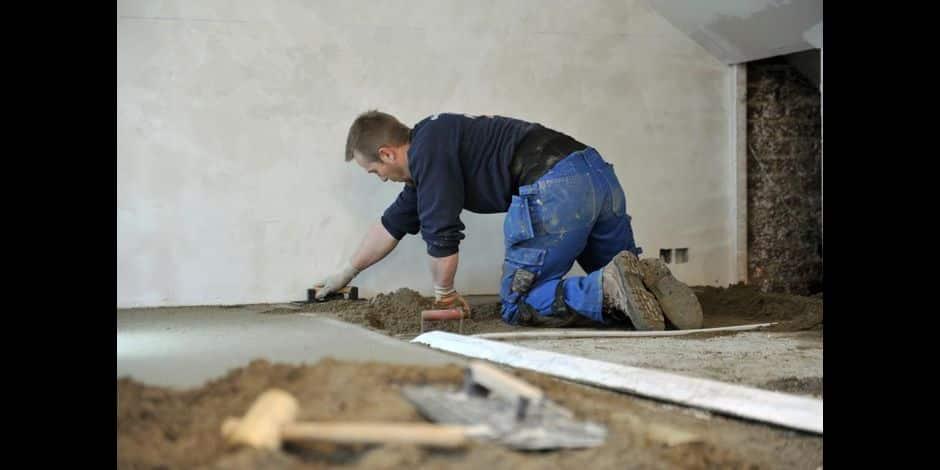 Maison en travaux pour restauration : des ouvriers en bâtiment restaurent les murs et le sol.