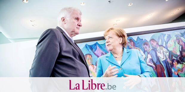 In this Wednesday, June 13, 2018 photo, German Chancellor Angela Merkel, right, talks to Interior Minister Horst Seehofer, left, prior to the weekly cabinet meeting at the chancellery in Berlin. (Michael Kappeler/dpa via AP)