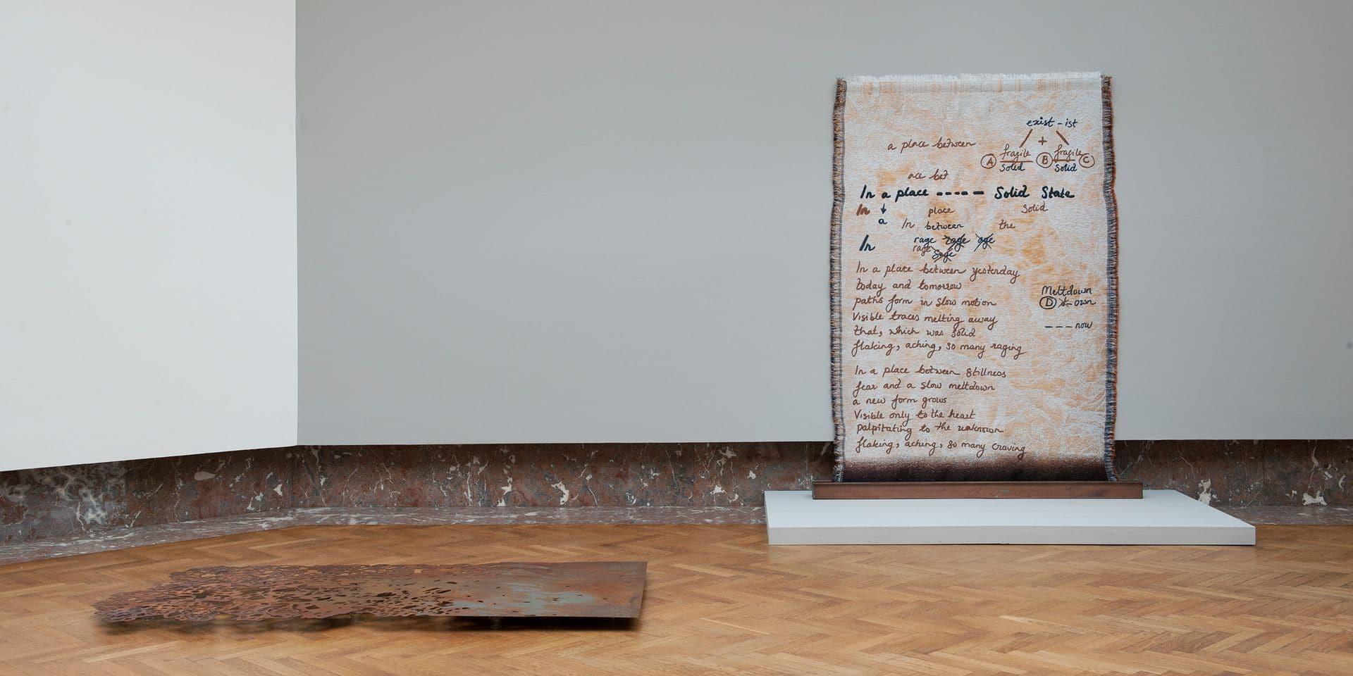 """Otobong Nkanga, vue partielle de l'installation à Bozar pour le BAP 2017, en avant plan: «Steel to Rust – Resistance», 2017; au mur: """" In a Place Yet Unknown"""", 2017, textile tissé et métal."""