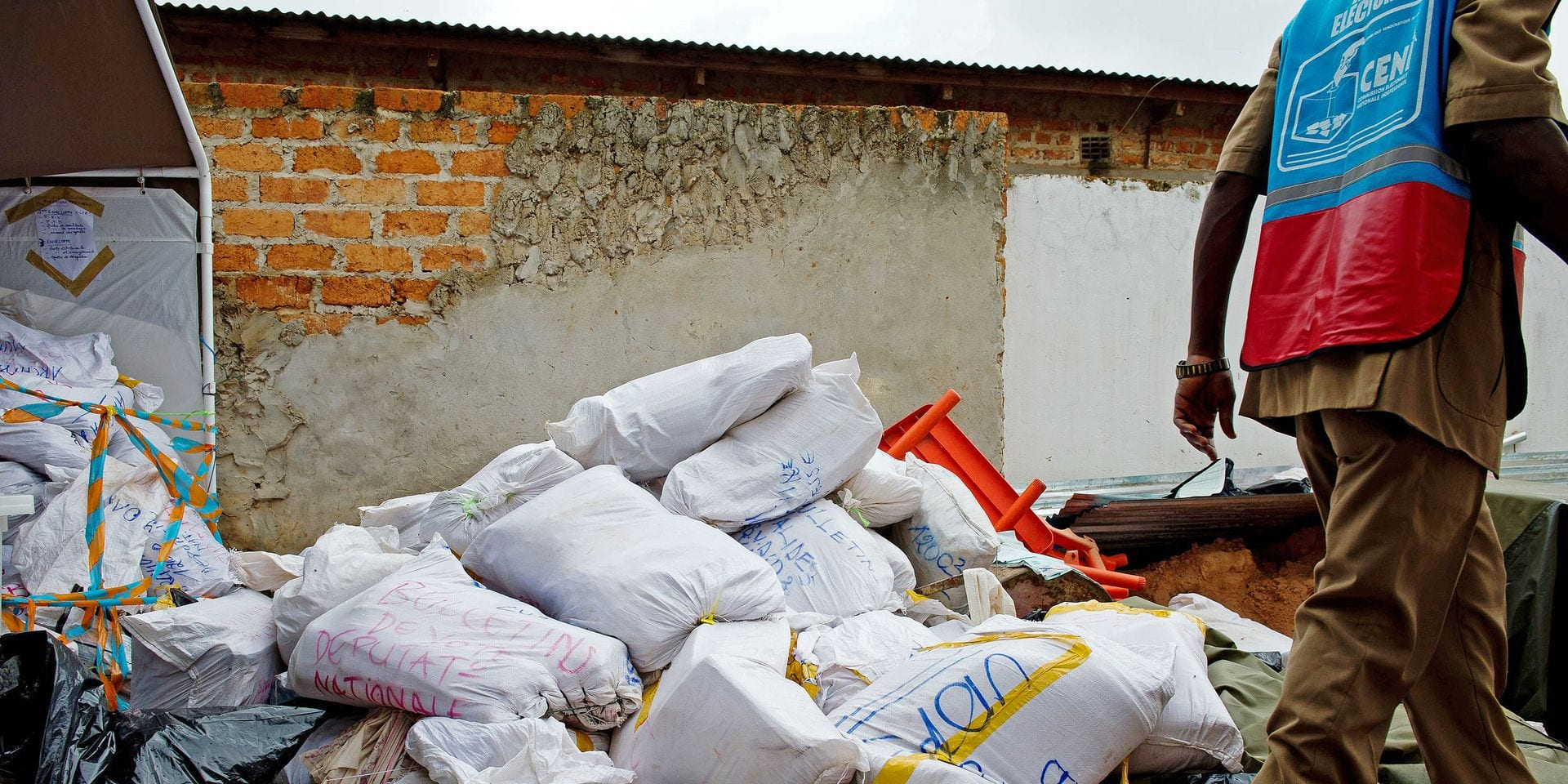 A Congolese electoral agent walks past a pile of bags of ballot papers at the National Independent Electoral Commission (CENI) in Lubumbashi on December 5, 2011. The announcement of the official provisionary results are expected tomorrow for the Democratic Republic of the Congo's presidential elections which took place last Monday, which have been marred by claims of fraud and a lack of transparency by opposition candidates. AFP PHOTO / PHIL MOORE (Photo by PHIL MOORE / AFP)