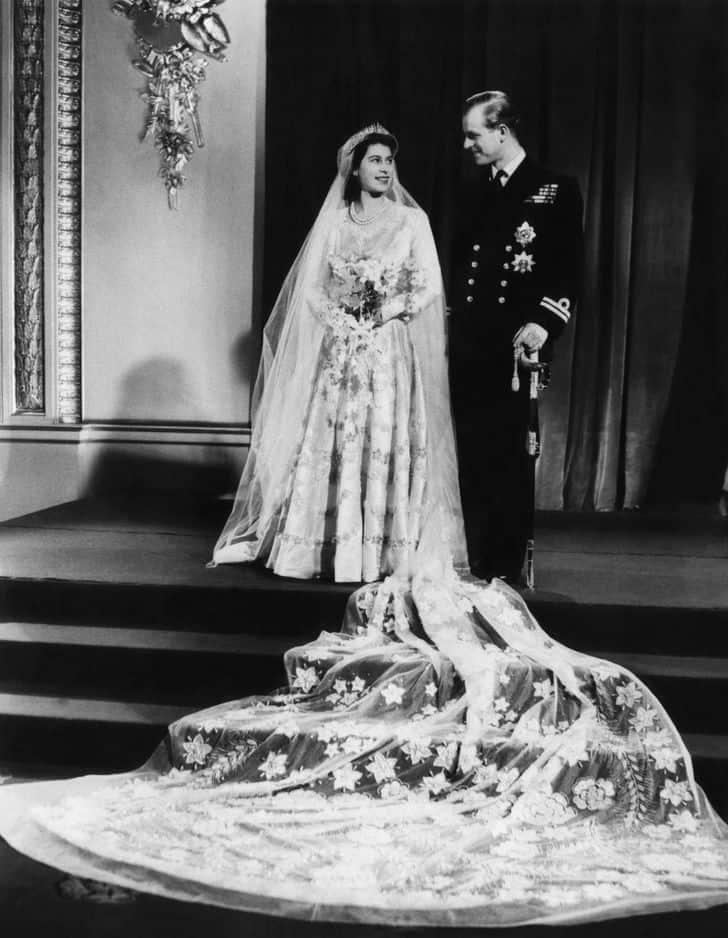 Le design de la robe d'Elizabeth, mariée en 1947, aurait été inspiré par une peinture de Botticelli, selon son créateur Norman Hartnell. Satin, dentelle fleurie, perles importées d'Amérique et du cristal la composent. La reine aurait utilisé des                   coupons de rationnement pour se les procurer.