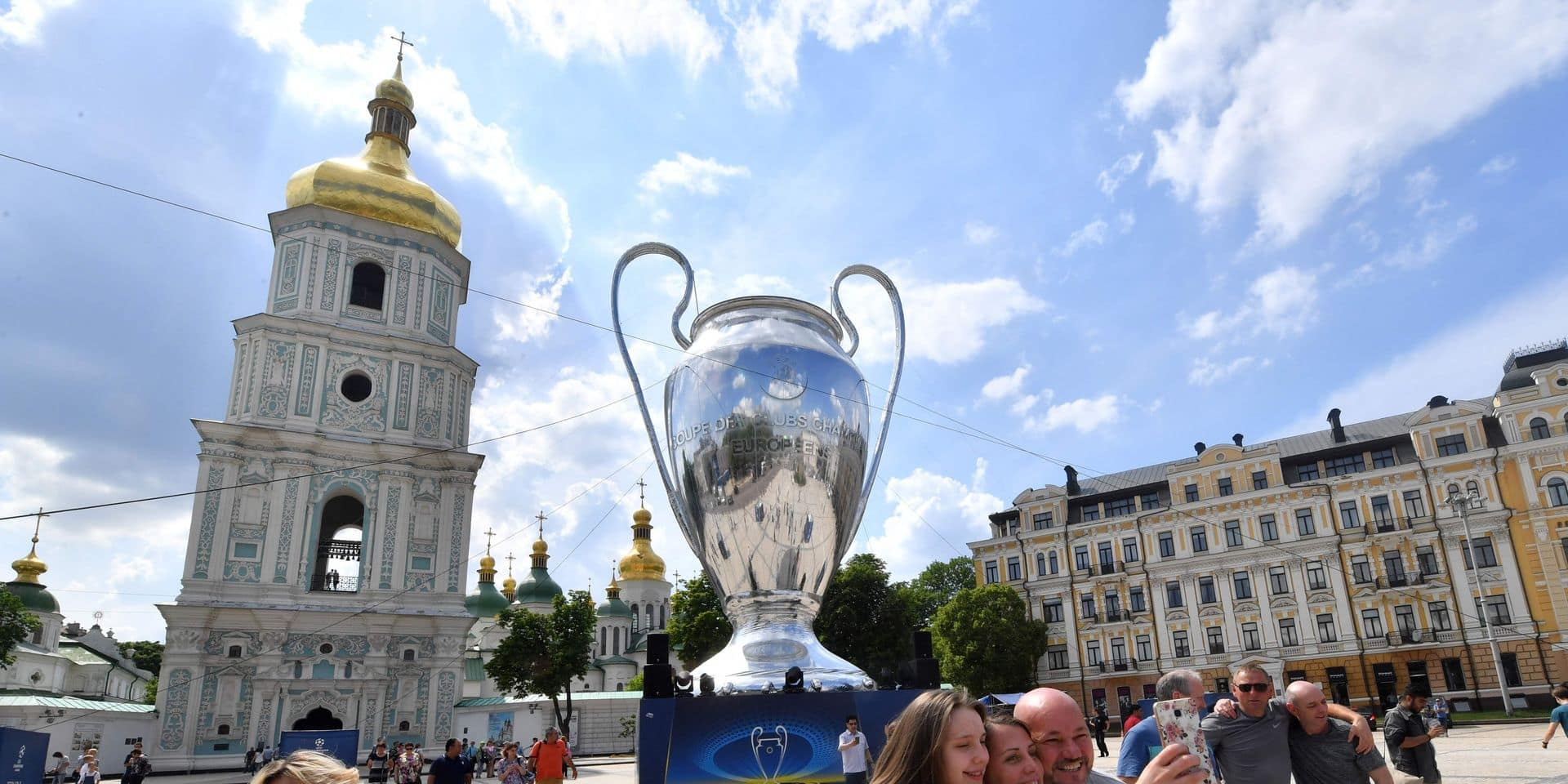 People make selfies with a huge trophy set in the Ukrainian capital of Kiev on May 25, 2018, a day before of the 2018 UEFA Champions League Cup final football match between Real Madrid and Liverpool FC at the Olimpiyskiy Stadium. / AFP PHOTO / Sergei SUPINSKY
