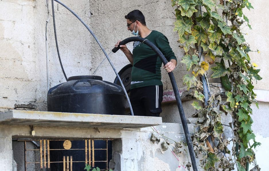 Un Palestinien remplit le réservoir de sa maison avec de l'eau achetée et livrée par un camion d'une entreprise locale qui extrait l'eau des puits et la vend aux gens, dans la ville de Khan Yunis, au sud de la bande de Gaza, le 18 novembre 2020.