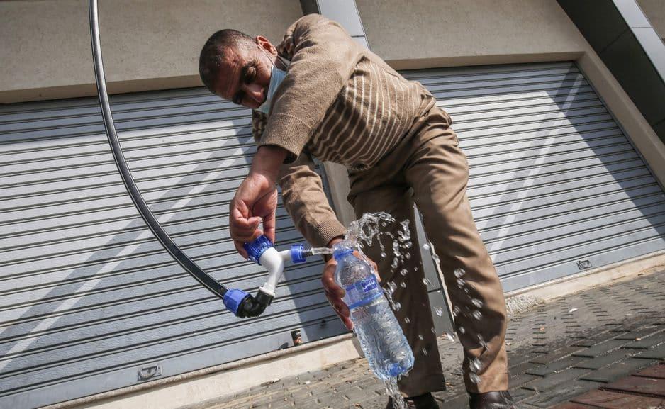 Un Palestinien remplit une bouteille à partir d'un générateur d'eau alimenté par l'énergie solaire.