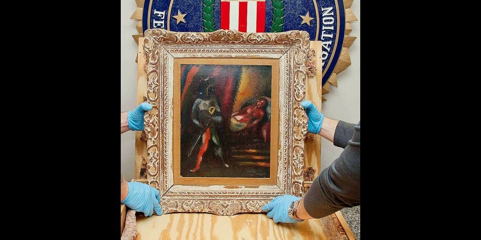 This photo obtained April 12, 2018 courtesy of the FBI in Washington,DC shows personnel from the FBI's Art Crime Team holding a framed work by Marc Chagall prior to its return to the owners' estate nearly 30 years after it was stolen. Nearly 30 years after an elderly New York couple's 1911 painting by Marc Chagall was stolen from their Manhattan home, the modernist oil-on-canvas work is being returned to the family's estate. The painting, entitled Othello and Desdemona, was recovered last year after a Maryland man contacted the FBI's Washington Field Office. / AFP PHOTO / FBI / Handout / RESTRICTED TO EDITORIAL USE - MANDATORY MENTION OF THE ARTIST UPON PUBLICATION - TO ILLUSTRATE THE EVENT AS SPECIFIED IN THE CAPTION