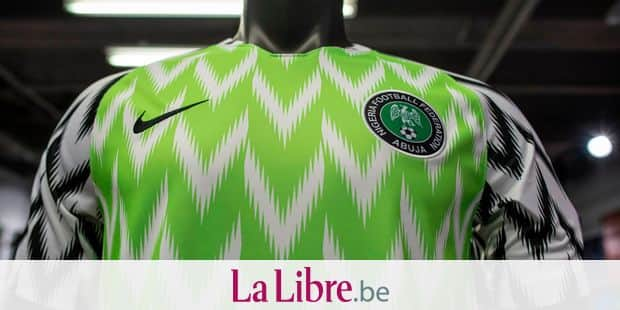 The Nigeria Super Eagles jersey for the 2018 World Cup in Russia is seen in a Nike store in Lagos on June 4, 2018. The Nigeria Super Eagles jersey for the 2018 World Cup in Russia has been hugely popular, both domestically and internationally, with fans scrambling to get their hands on the white and lime green coloured jersey. In Nigeria, where poverty is widespread, many can't afford the official kit, so they buy fakes imported from Asia. / AFP PHOTO / STEFAN HEUNIS