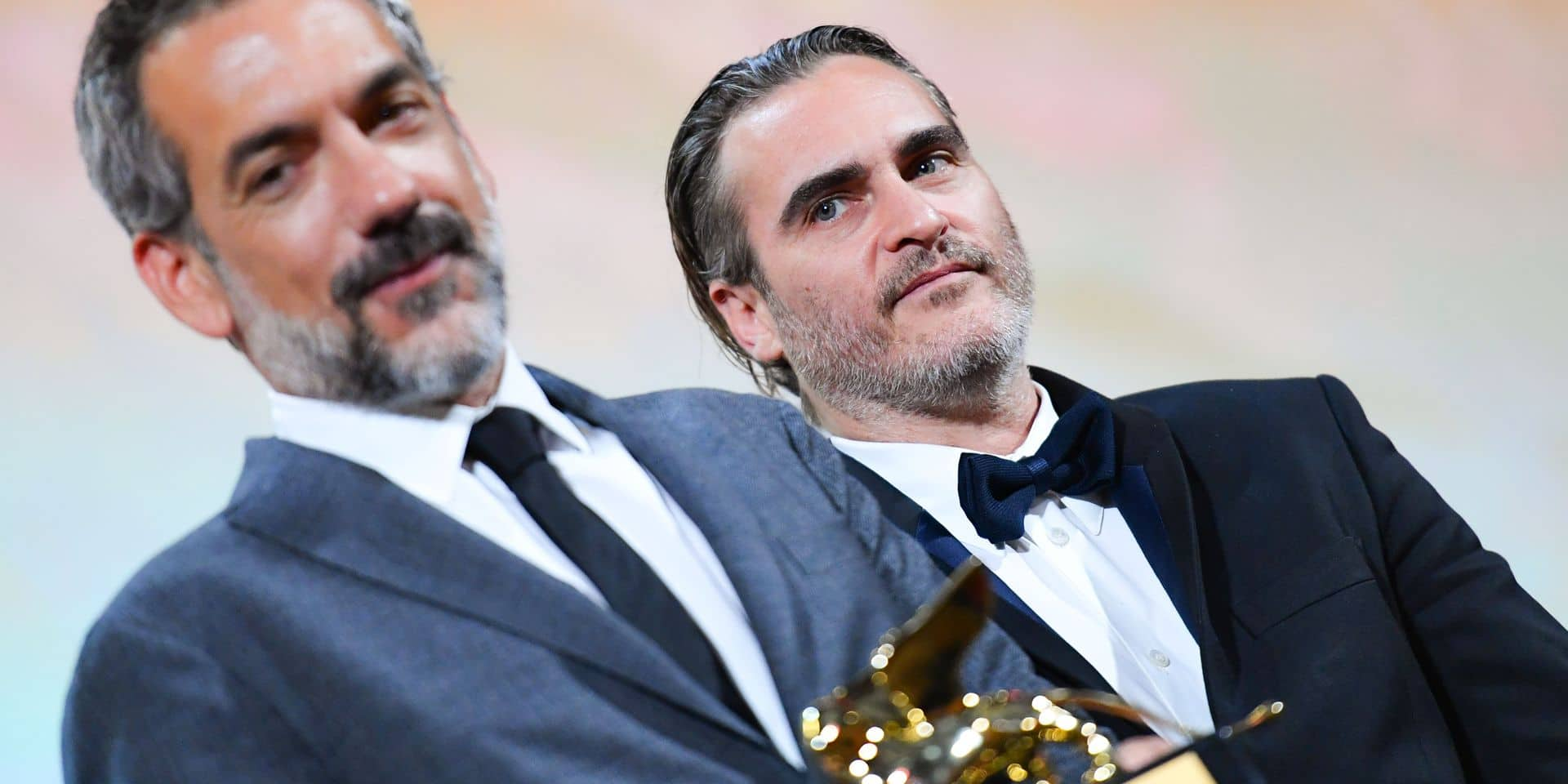 "US director Todd Phillips (L), flanked by US actor Joaquin Phoenix, holds the Golden Lion award for Best Film he received for the movie ""Joker"" during the awards ceremony of the 76th Venice Film Festival on September 7, 2019 at Venice Lido. (Photo by Alberto PIZZOLI / AFP)"