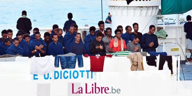 """Migrants pray aboard the Italian Coast Guard ship """"Diciotti"""" moored at the Catania harbor Wednesday, Aug. 22, 2018. The European Union is trying to find countries willing to take 177 people rescued at sea after Italy sought its help to deal with yet another migrant standoff with Malta. The Italian coast guard ship Diciotti that had been sitting off Italy's Lampedusa island entered Catania's harbor. Rome asked Malta to take them in but Malta, the EU's smallest member country _ refused, saying the migrant boat wasn't in distress and that the migrants declined Maltese assistance, preferring to continue toward Italy. (Orietta Scardino/ANSA via AP)"""
