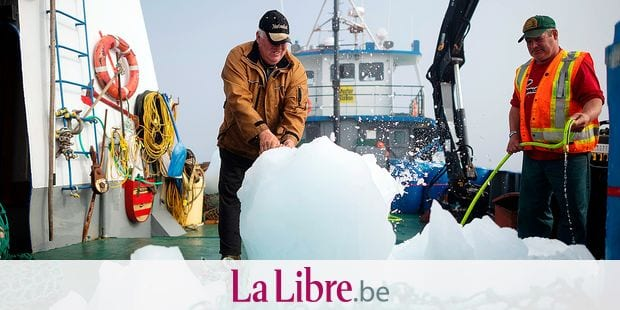 """Captain Edward Kean (L) crushes pieces of an iceberg, while Phil Kennedy cleans the salt water, as they sail in Bonavista Bay on June 30, 2019 in Newfoundland, Canada. - Iceberg water, considered pure, is now marketing for a unique sector of high-end products. """"We are trying to target the niche market for healthy foods and products,"""" says former fisherman Edward Kean, an iceberg hunter. For 20 years, he has been cruising the North Atlantic aboard his fishing boat to retrieve chunks of ice to melt and sell the water to local traders. Customers include manufacturers of vodka, cider, liquor, beer, cosmetics, but also companies that bottle water. (Photo by Johannes EISELE / AFP)"""