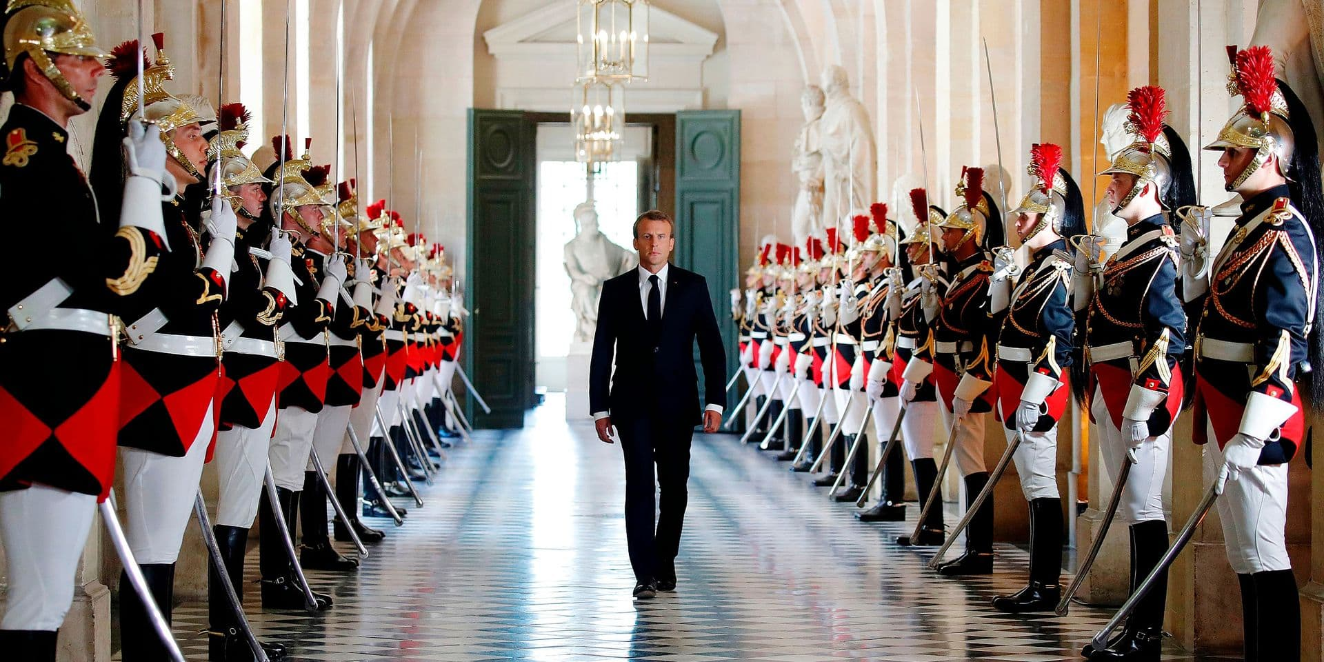 French President Emmanuel Macron walks through the Galerie des Bustes (Busts Gallery) to access the Versailles Palace's hemicycle to address both the upper and lower houses of the French parliament (National Assembly and Senate) at a special session in Versailles near Paris, France, July 9, 2018. The French President will gather both houses of parliament at the opulent Versailles Palace on July 9 for what has become an annual address on his plans for overhauling wide swathes of French society and institutions. / AFP PHOTO / POOL / CHARLES PLATIAU