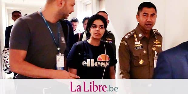 "CORRECTION - This handout picture taken and released by the Thai Immigration Bureau on January 7, 2019 shows 18-year-old Saudi woman Rahaf Mohammed al-Qanun (C) being escorted by a Thai immigration officer (R) and United Nations High Commissioner for Refugees (UNHCR) officials at Suvarnabhumi international airport in Bangkok. - Rahaf Mohammed al-Qunun, seeking asylum has left Bangkok airport ""under the care"" of the UN refugee agency, a Thai official said on January 7, following her desperate plea against deportation. (Photo by Handout / Thai Immigration Bureau / AFP) / -----EDITORS NOTE --- RESTRICTED TO EDITORIAL USE - MANDATORY CREDIT ""AFP PHOTO / THAI IMMIGRATION BUREAU"" - NO MARKETING - NO ADVERTISING CAMPAIGNS - DISTRIBUTED AS A SERVICE TO CLIENTS / ""The erroneous mention[s] appearing in the metadata of this photo has been modified in AFP systems in the following manner: [adding handout restrictions]. Please immediately remove the erroneous mention[s] from all your online services and delete it (them) from your servers. If you have been authorized by AFP to distribute it (them) to third parties, please ensure that the same actions are carried out by them. Failure to promptly comply with these instructions will entail liability on your part for any continued or post notification usage. Therefore we thank you very much for all your attention and prompt action. We are sorry for the inconvenience this notification may cause and remain at your disposal for any further information you may require."""