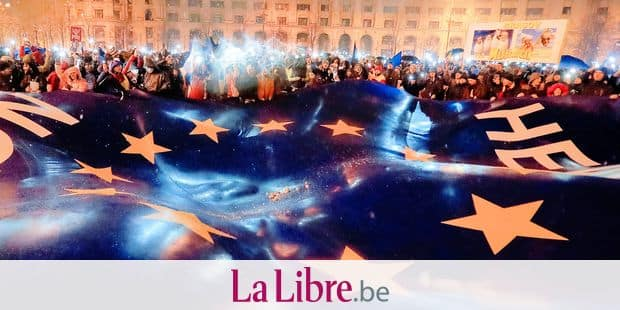 """FILE - In this Saturday, Jan. 20, 2018, file picture people shine the lights of their mobile phones next to a large European Union flag bearing the words """"Here_Now"""" during a protest outside the parliament building in Bucharest, Romania. Romanian officials have slammed European Union officials for treating it as """"a second-rate"""" country as it prepares to take over the EU's rotating presidency. (AP Photo/Vadim Ghirda, File)"""