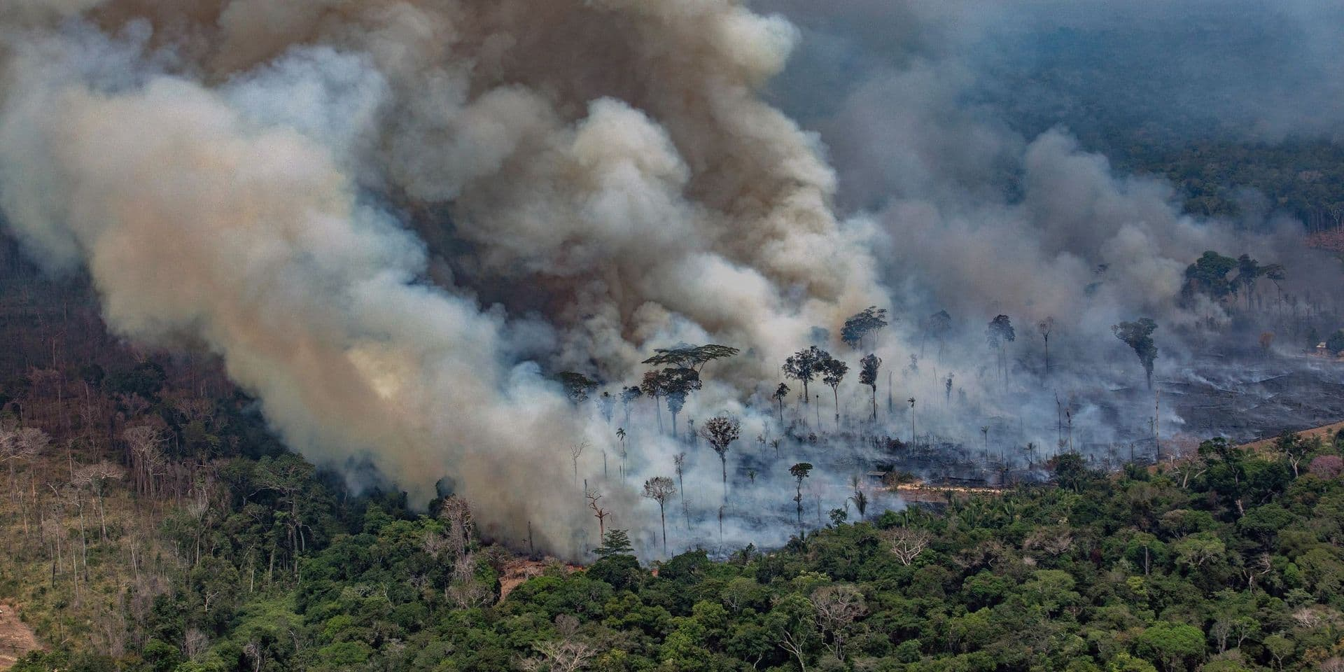"""TOPSHOT - Handout aerial released by Greenpeace showing smoke billowing from forest fires in the municipality of Candeias do Jamari, close to Porto Velho in Rondonia State, in the Amazon basin in northwestern Brazil, on August 24, 2019. - Brazil on August 25 deployed two Hercules C-130 aircraft to douse fires devouring parts of the Amazon rainforest. The latest official figures show 79,513 forest fires have been recorded in the country this year, the highest number of any year since 2013. More than half of those are in the massive Amazon basin. Experts say increased land clearing during the months-long dry season to make way for crops or grazing has aggravated the problem this year. (Photo by Victor MORIYAMA / GREENPEACE / AFP) / RESTRICTED TO EDITORIAL USE - MANDATORY CREDIT """"AFP PHOTO / GREENPEACE / VICTOR MORIYAMA"""" - NO MARKETING - NO ADVERTISING CAMPAIGNS - NO RESALE - NO ARCHIVE - IMAGE AVAILABLE FOR PUBLICATION AND DOWNLOAD UNTIL 09.09.2019 - DISTRIBUTED AS A SERVICE TO CLIENTS /"""