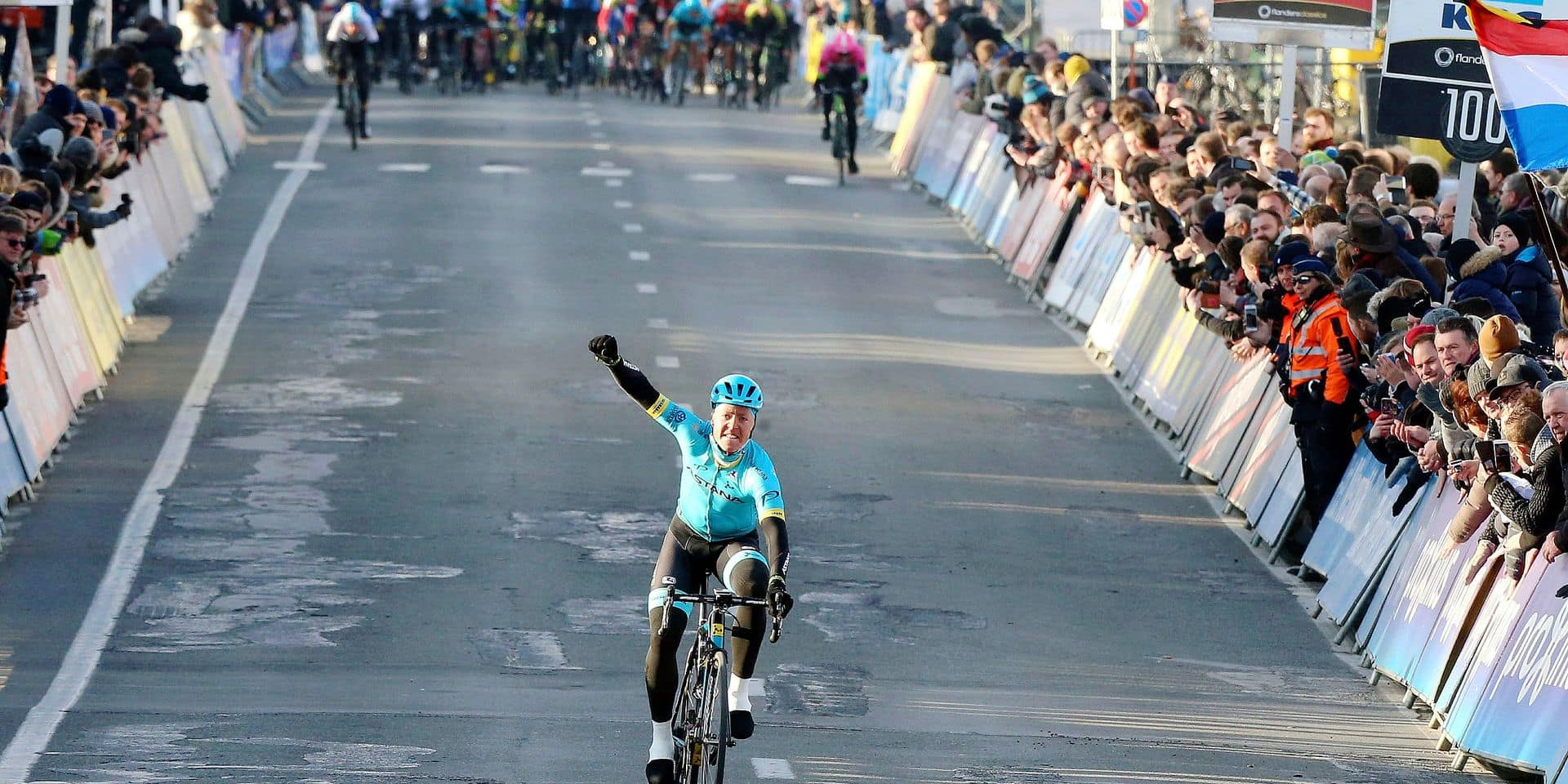 Denmark's Michael Valgren Andersen from the Astana team raises his fist as he crosses the finish line to take first place in the Omloop Het Nieuwsblad in Ninove, Belgium on Saturday, Feb. 24, 2018. (AP Photo/Francois Walschaerts)