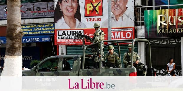 This June 21, 2018 photo, shows a military patrol drive past a political propaganda banner for Laura Caballero, a candidate for the Guerrero state legislature from the Labor Party, and presidential candidate for the MORENA party Andres Manuel Lopez Obrador, in Acapulco, Mexico. Three years ago Caballero closed her restaurant on Acapulco's main tourist drag after organized crime tried to extort her. (AP Photo/Marco Ugarte)