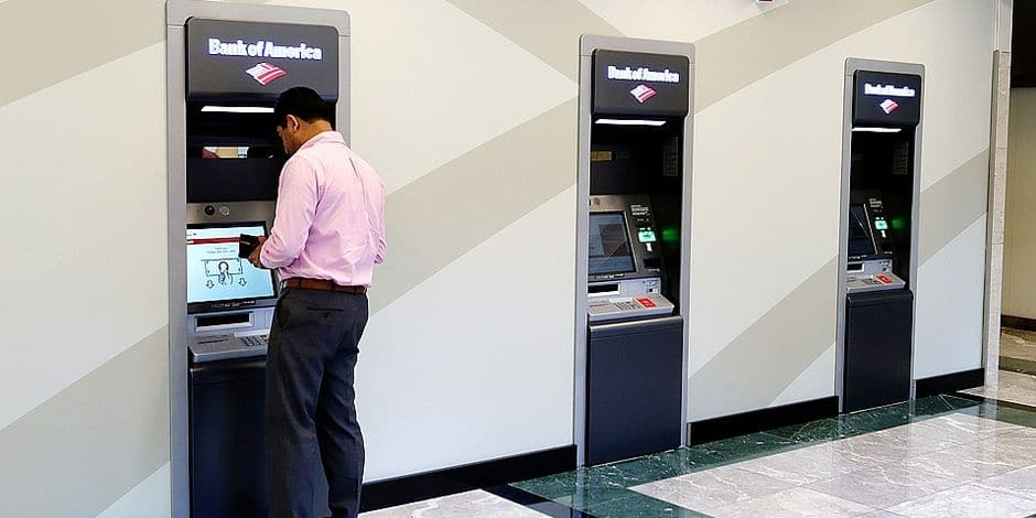FILE- In this July 9, 2018, photo, a customer makes a transaction at a Bank of America ATM at the company's headquarters in Charlotte, N.C. Bank of America Corp. reports earnings Monday, July 16. (AP Photo/Chuck Burton, File)