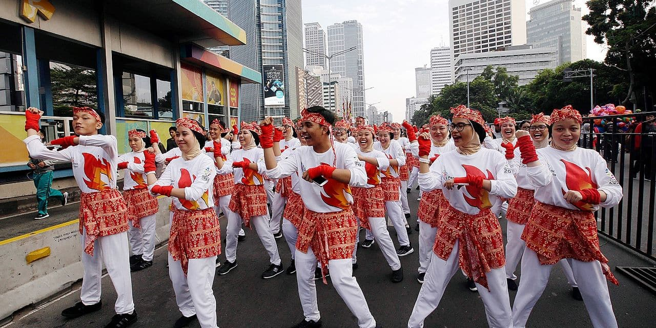 Indonesian students perform the country's traditional Poco-Poco dance in an attempt to break the Guinness World Record ahead of the Asian Games in Jakarta, Indonesia, Sunday, Aug. 5, 2018. More than 60,000 people performed the collective dance on the main street. (AP Photo/Tatan Syuflana)