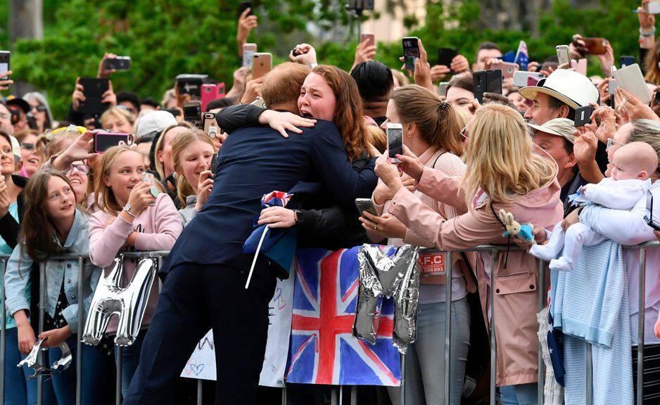 Une jeune fille qui attendait depuis deux heures du matin laisse éclater sa joie en serrant (un peu trop) fort Harry dans ses bras.