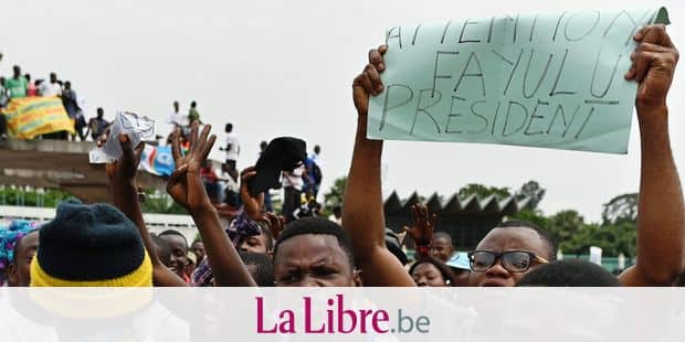 """Supporters of opposition presidential candidate in the Democratic Republic of Congo, Martin Fayulu hold up a placard reading """"Caution: Fayulu president"""" as they sing the Constitutional Court in Kinshasa on January 12, 2109 with his wife Esther after he filed his appeal to impose a recount of the votes in the presidential election following a suspicion of fraud. - The outcome of DR Congo's tempestuous presidential election appeared to be headed for the courts on January 11 after the poll's runner-up said he would demand a recount. Martin Fayulu, an opposition candidate tipped by pollsters as the likely winner of the December 30 vote and who came in a close second, dismissed the result and announced he will challenge the outcome before the Constitutional Court. (Photo by TONY KARUMBA / AFP)"""