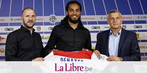 Olympique Lyonnais' football newly recruited defender, Belgium's Jason Denayer (C) poses with his new jersey next to head of Lyon's recruitment unit Florian Maurice (L) and Lyon's French head coach Bruno Genesio (R) during his official presentation, on August 22, 2018 at the Parc Olympique Lyonnais in Decines-Charpieu, near Lyon eastern France. (Photo by PHILIPPE DESMAZES / AFP)