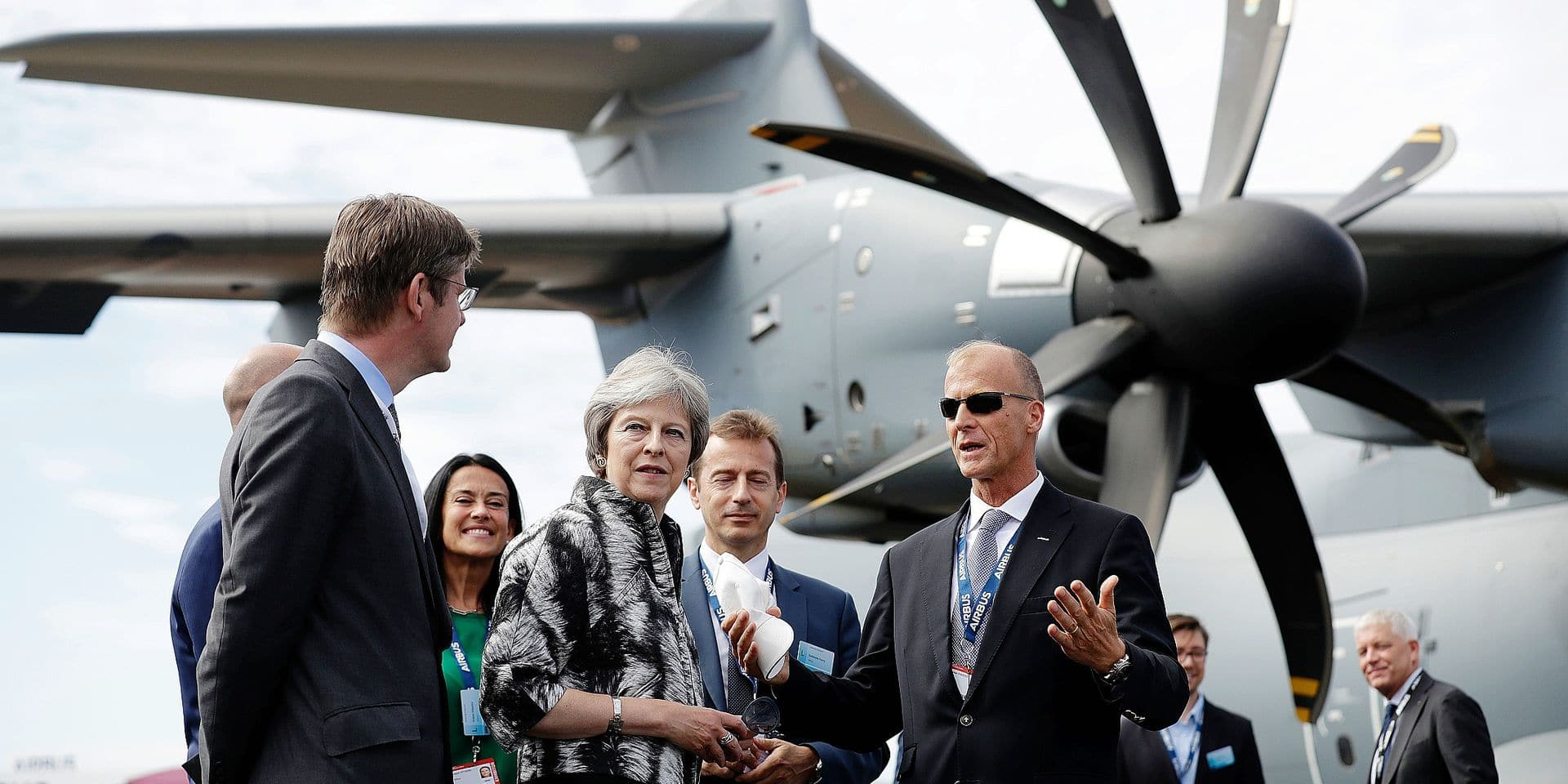 British Prime Minister Theresa May, second left speaks with Airbus CEO Tom Enders, right, from Germany, backdropped by an Airbus A400M Atlas military transport aircraft at the Farnborough Airshow in Farnborough, England, Monday, July 16, 2018. (AP Photo/Matt Dunham)