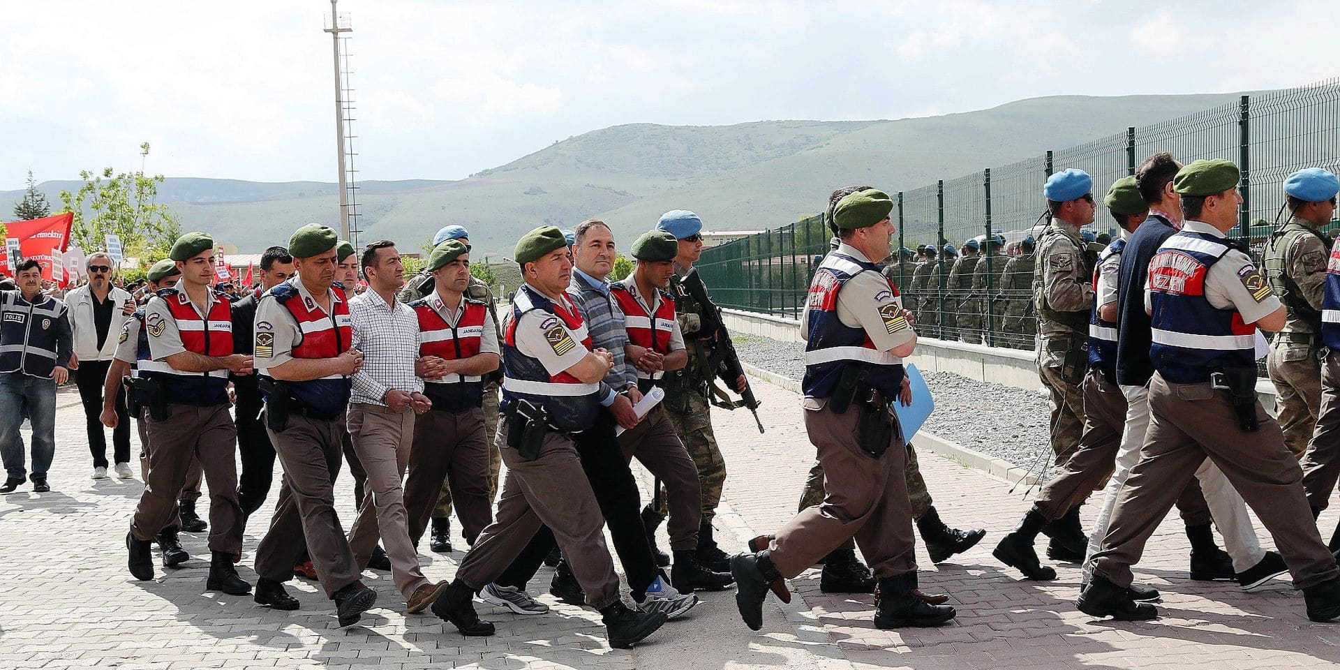 Arrested soldiers accused of being involved in an attempted coup d'etat on 15 July 2016 in Turkey, are accompanied by Turkish soldiers as they arrive at the court inside the Sincan Prison in Ankara, on May 22, 2017 to be trialed. The trial opened on May 22, 2017 of more than 220 suspects, including over two dozen former Turkish generals, accused of being among the ringleaders of the attempted coup last year aimed at ousting President Recep Tayyip Erdogan. / AFP PHOTO / ADEM ALTAN