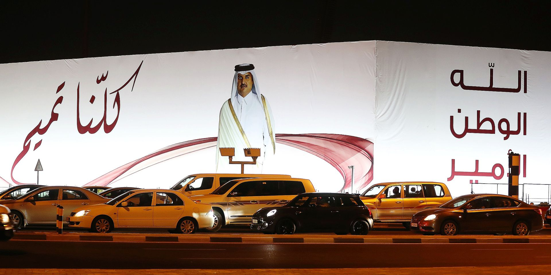 """(FILES) In this file photo taken on June 11, 2017 A general view taken on June 11, 2017 shows a portrait of Qatar's Emir Sheikh Tamim bin Hamad Al-Thani and text reading in Arabic: """"We are all Tamim"""" on a billboard outside the Qatar Sports club in Doha after the diplomatic crisis surrounding Qatar and the other Gulf countries spilled from social media to more traditional forms of media -- all the way back to billboards. The year-old acrimonious dispute between Qatar and its neighbours is forging a """"new"""" Gulf, potentially transforming what was a stable region of the Arab world, experts warn. / AFP PHOTO / Karim JAAFAR"""