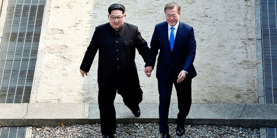 North Korean leader Kim Jong Un, left, and South Korean President Moon Jae-in cross the military demarcation line at the border village of Panmunjom in Demilitarized Zone Friday, April 27, 2018. Their discussions will be expected to focus on whether the North can be persuaded to give up its nuclear bombs. (Korea Summit Press Pool via AP)